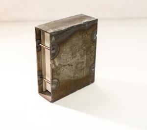 Small silver, rusted book with two bars on the spine, the pages shown.