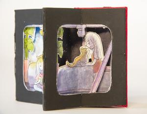 A black pop-up book. Inside the illustration is of a girl sitting on her bed, her cat on top of her.