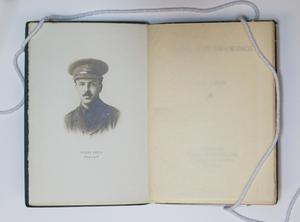 A book open to two pages. The page on the left is a photo of a mustached man in army uniform, the page on the right is blank.
