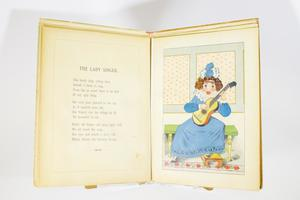 "An open book with the left page containing a short poem titled ""The Lady Singer"" and the page on the right containing a movable illustration of a puppet-like lady in a bright blue dress playing a guitar as she sits on a green bench with her foot on a tan step stool. The illustration is made movable by a tab you pull at the bottom."
