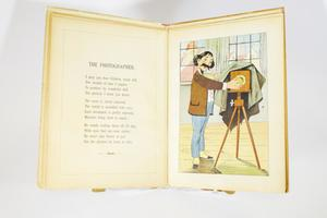 "A movable image of a puppet-like image of a man with a mustache and short hair standing by a camera on a tripod, a cloth over it as he stands in a room with big windows. The image is made movable by tabs at the bottom. The page on the left contains a poem titled ""The Photographer."""