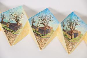 Closeup of three sections of a triangular book, showing a painting on each part of a small house with a bare tree in front of it.