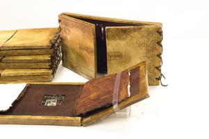 Brown wooden book, open to a brown inside. Behind them is another book seen from the cover.