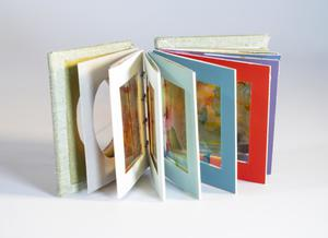 A small book open, each page a different pastel color. Each page also has a clear sheet on it.