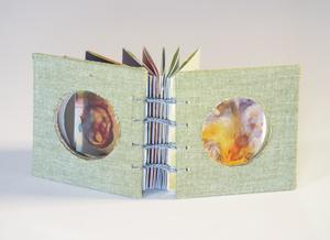 A small book bound togehter with light blue string. The front and back have a circle cut out.