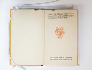 A book open to the inside. The page on the left is blank, the page on the right is the title page, an orange stamp in the middle.