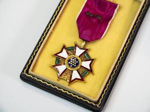 A circular medal with five leaves around it that are white in color, rimmed by red. The circle in the middle is blue and rimmed by gold, with little gold dots inside of it. It is attached to a velvet red ribbon, and laying in a black box layed with gold material.
