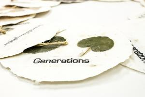 Closeup of a white paper circle, dried green leaves on it. The word Generations is under it in black.