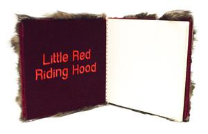 Open book with fur seen from the cover. The left page is a velvety red with the words Little Red Riding Hood on it in bright red letters. The right side is a blank white page.