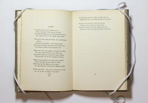 Open book, the page on the left containing a song titled Glory. It is continued on the top of the right page, the reest of it being blank.