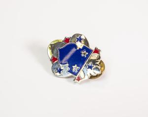 A pin of a bue crest surrounded by silver with 3 red and 4 blue stars in the silver part of it.