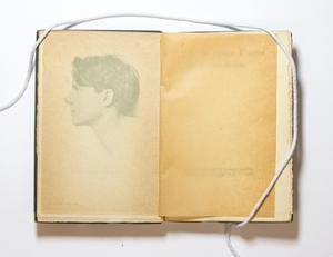 A book open, the left page contaaing a side view of a mans head.