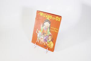 A red book cover containing an illustration of a giant old man, a space-like background over the back of his head. He is standing over Dorothy and her friends fom the Wizard of Oz. The title is at the top in yellow letters.