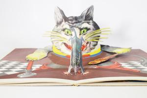 Pop-up of giant cat's head, its paws also sticking out of the page with one holding a spoon. Directly in front of it is a mouse running away, two paws on the floor.