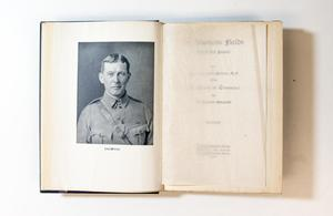 An open book, the page on the left containing a photo of a soldier, the page on the right is blank.
