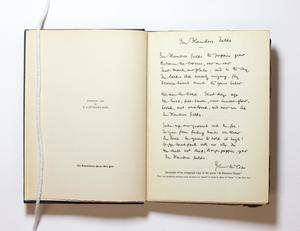 An open book, the page on the left contains the title in the middle. The page on the right has a note written by hand in black ink.