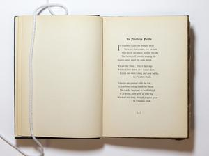 An open book, the page on the left blank and the page on the right containing a poem titled In Flaunders Fields.