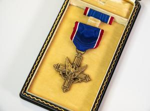 A bronze cross with a symbol of an eagle over it. It is attached to a blue ribbon with a red line on each side, and laying in a box that is a yellow on the inside.