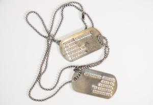 Two metal dog tags attached to the same chain looped at the top of each. The words carved on the tags are barely visible.