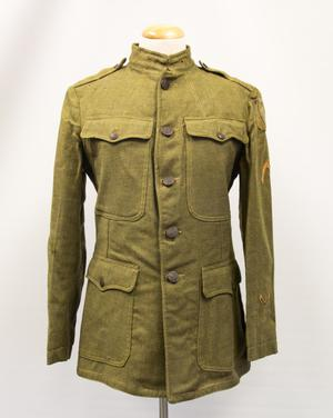 Green wool jacket, several buttons down the middle of it. It has a breast pocket on each side with a button. It also has a button on the collar,  and two pockets on each side on the bottom front. On the left sleeve is  a yellow arrow on the bottom of it, another yellow design is partially  seen on the left shoulder.