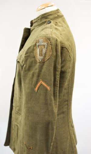 Side view of a green wool jacket. It is seen from the left side, on it a yellow arrow patch, and a cross patch on the shoulder.