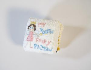 A small white fabric book, a tooth fairy and the words knitted on there.