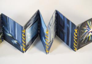 Book open like an accordion, dark blue in color and painted on. It is tied together with yellow string.