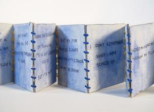 A light blue book open like an accordion, with writing on each page. It is tied together with blue string.