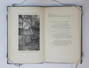 An open book, the page on the left a photograph of a woman wearing a gas mask and long dress. The page on the right titled at the top, text underneath it.