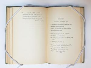 A book open, the page on the left containing a bit of text. The page on the right containing text titled Good-By.