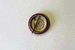 The back of a pin, red around the rim. There are some words printed on the inside of it.