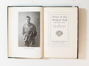 An open book, the left page contains a photograph of a soldier in uniform. The right page contains the title page.