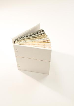 A small thin book, bound together with string and white in color. They are slightly open.