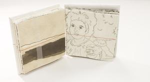 A small white book, open. The left page is white and has black painted on it. The right page contains a drawing of a young girl on it.