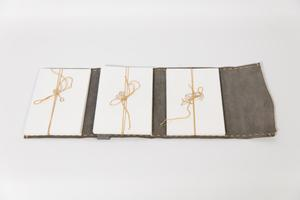 A grey leather bound book, opened up with three paper, bound together with string.