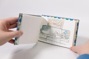 Small open book, a painting on the right page of someone laying down on a couch.