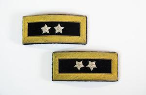 Two shoulder straps which are black in the middle and a faded yellow around the thick frame. Inside of each black part are two white stars.