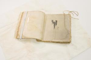 White book without a thread. On the left page, a white cord is over it. It is laying on a white cloth.