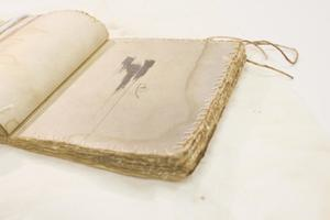 White book without a thread. On the left page, a white cord is over it. It is laying on a white cloth. The book pages are threaded.