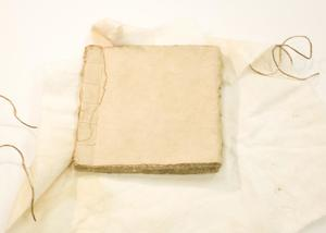 Book without a cover on a white cloth with a thread over it.