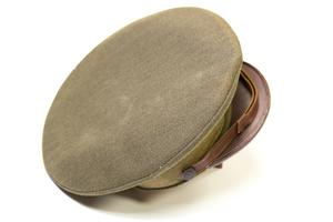 A circular green army cap, a brown visor attached to it.
