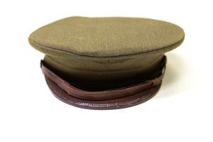 Front view of a circular green army cap, a brown visor attached to it.