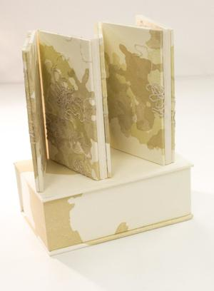 White and yellow book.  There is one closed and propped up, and another one opened up on top of it.