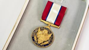A medal made up of a navy blue circle with gold lettering aroud the rim of it. Inside is a detailed gold emblem, and the medal hand from a red and white ribbon long with thin lines of blue. The medal lays inside of a container.
