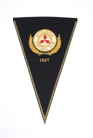 A black triangular flag, a circle with the words Mitsubishi Football Club on it in yellow. Under it is the date 1967 in yellow.