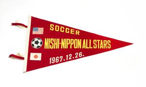 A red triangular flag. On the left side of it is the American flag, a soccer ball and the Japanese flag. To the right are the words Nishi-Nippon All Stars in yellow.