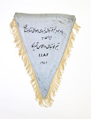 A light grey flag, fringed by yellowish thread. The middle of has text in a different language in black letters.