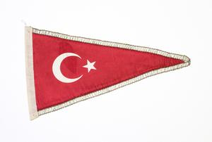 A rectangular flag, red in color and outlined by white. On the flag are moon and star shapes.