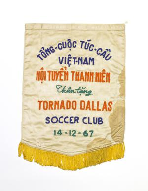 White flag fringed by yellow thread at the bottom. On the flag are the words Tornado Dallas in Orange, below that the words Soccer Club in in blue.