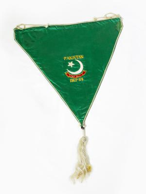 A green flag, a white fringe hanging from the tip of it. In the middle of the flag is the word Pakistan in small yellow letters, a white star and moon under it.
